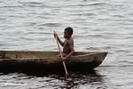Boy paddling a dugout canoe in a lagoon near Loango National Park