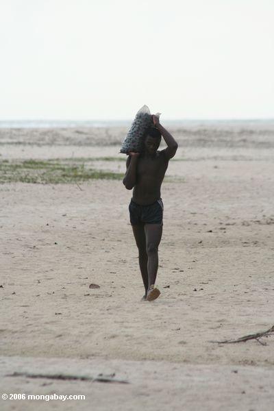 Músculos carregando de um homem na praia perto de St. Catherine do ponto