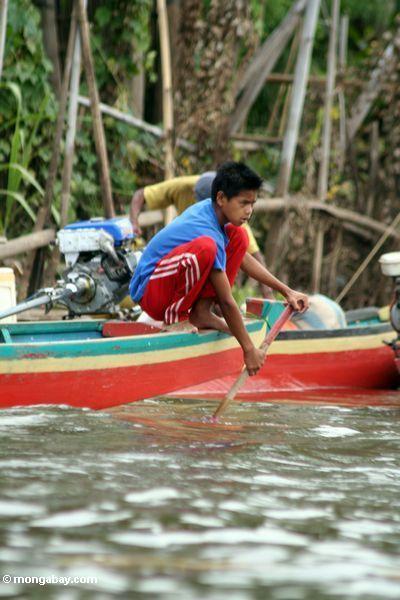 Junge, der ein traditionelles Boot nahe See Tempe Sulawesi