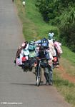 Vendor carrying his goods on a bike which he is pushing uphill along a highway in Uganda