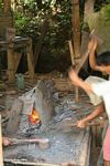 Metal workers pounding a hand knife into shape (Toraja Land (Torajaland), Sulawesi)